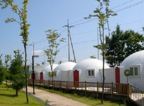 Group of tiny houses or safety shelters with red doors from InterShelter Inc.