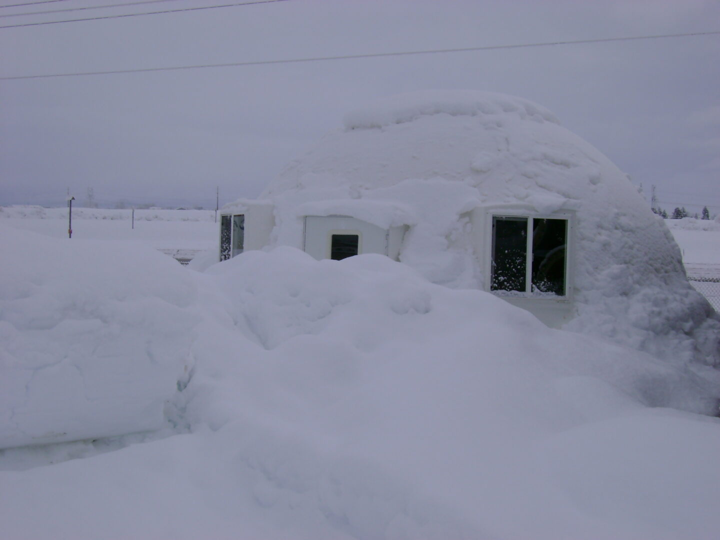 military-grade safety shelter from InterShelter Inc. covered by snow