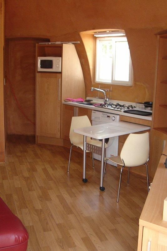 Tiny house with kitchen, dining, and laundry space from InterShelter Inc.